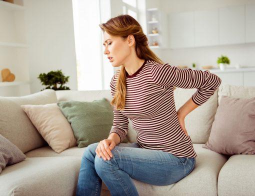 cálculo renal e pedra na vesícula: mulher com dores lombares sentada em sua casa