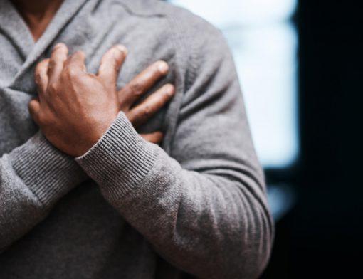 Colesterol alto causa dor no peito: pessoa pressionando peito em sinal de dor, algo que pode ser estimulado pelo colesterol alto.