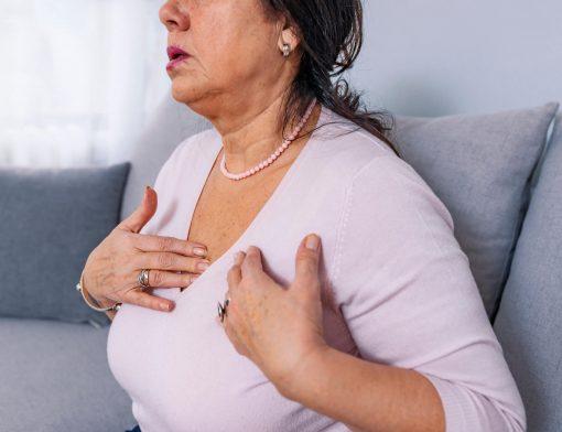 dor no peito ao respirar: senhora de idade sentindo dor ao respirar no sofá de casa, que pode ser derivada de Infecções no pulmão, tumores, etc.